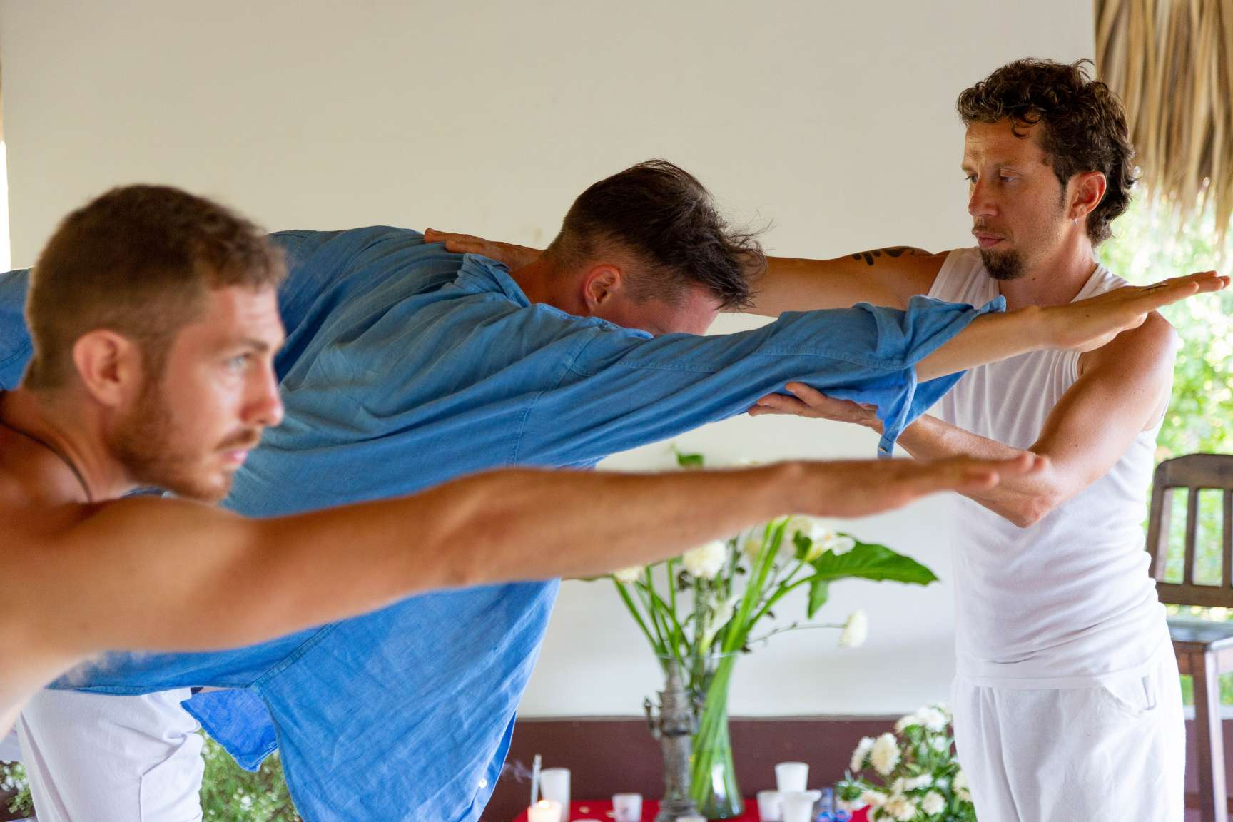 male yoga teacher assisting a young man in natarajasana