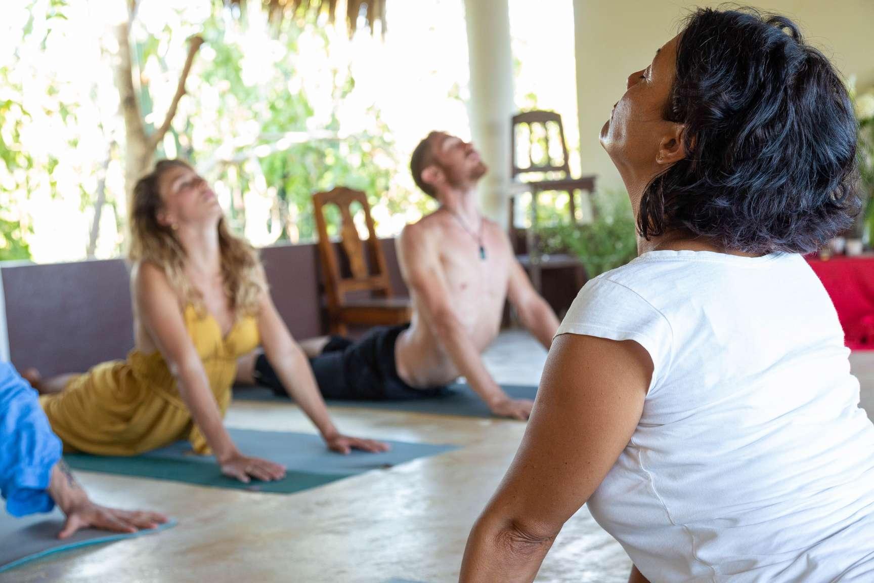 woman yoga teacher and students doing Bhujangasana