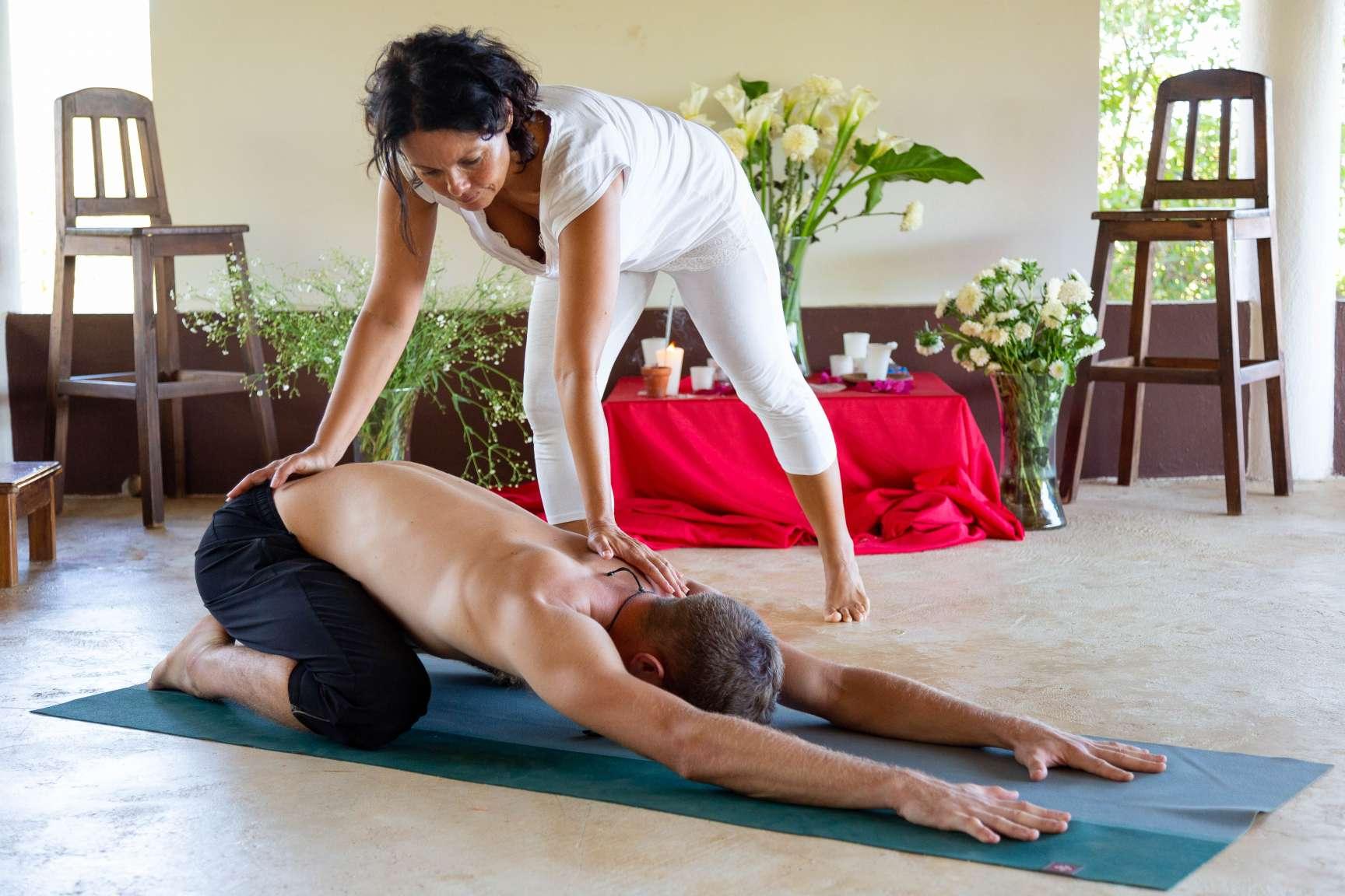 woman yoga teacher assisting man in Balasana