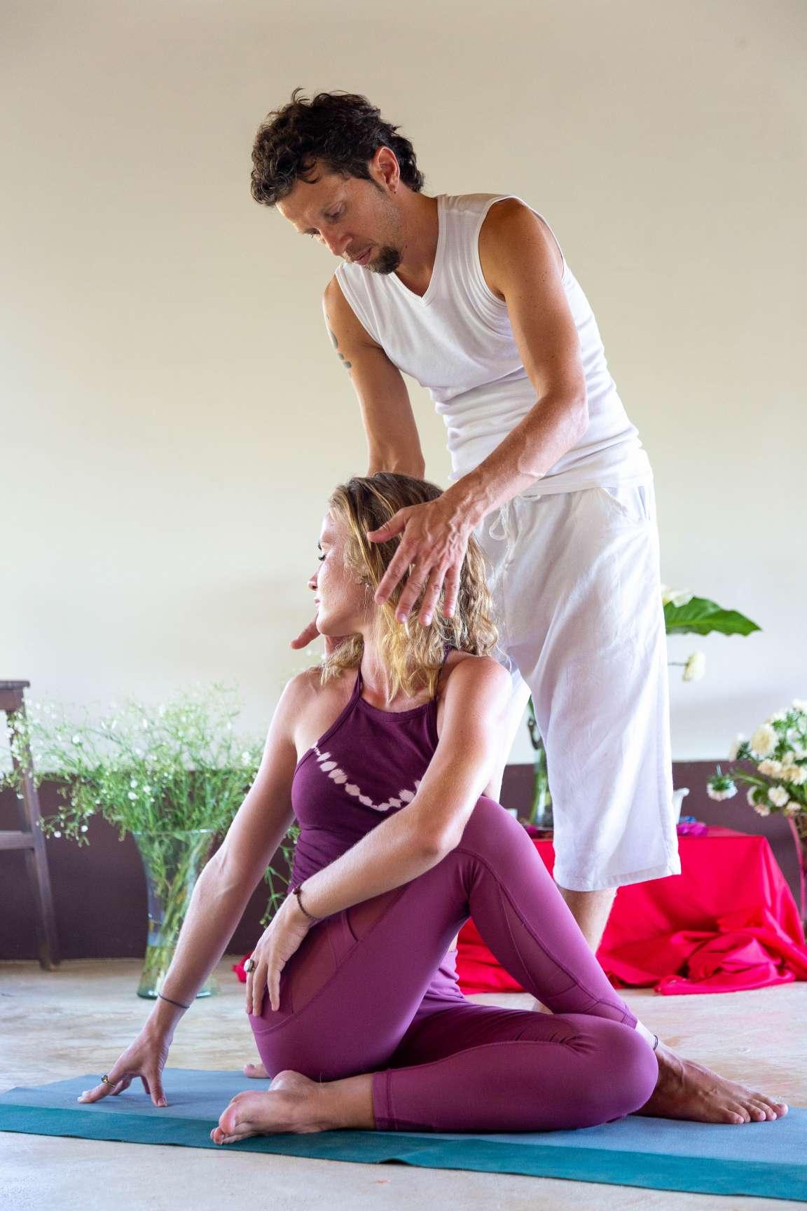 man yoga teacher assisting woman in twist yoga pose