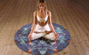 blond young woman meditating in lotus on a round yoga mat
