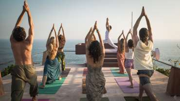 people in yoga warrior pose on roof top with ocean view at Yoga Teacher Training Course 200hr in Mexico