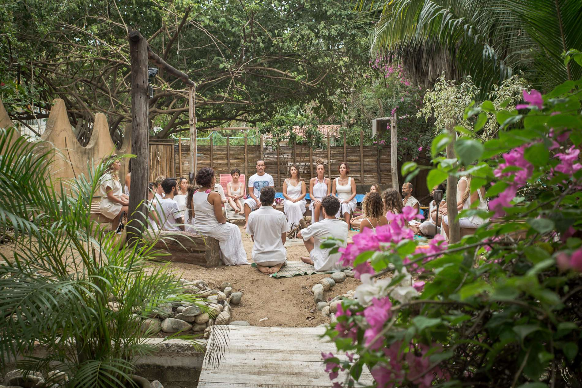 yoga group wearing white sitting in a circle in a beautiful patio surrounded by trees and flowers