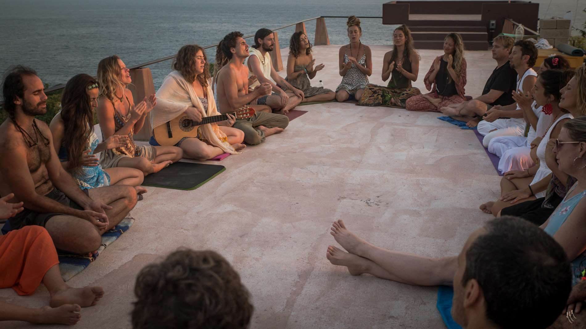 group of yoga teacher training students sitting in a circle chanting mantras