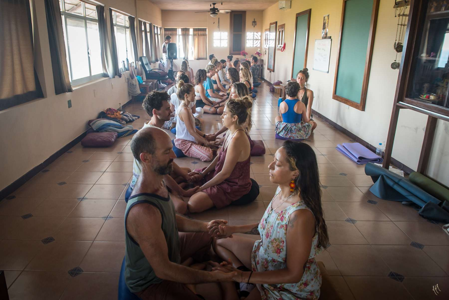 tantric couples meditating hand in hands in yoga studio