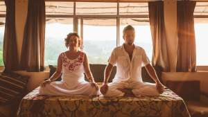 tantric woman and man sitting in meditation posture in front of windows at a Tantra Teacher training. The sun ist shining into the room
