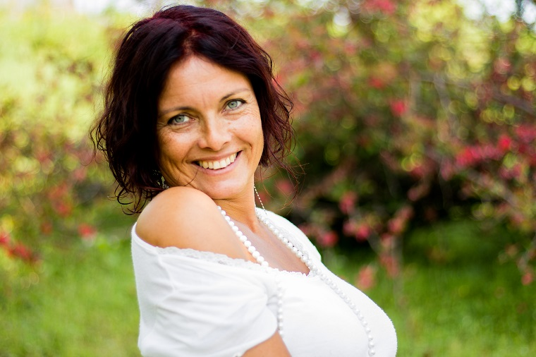 Portrait of a woman smiling in park with flowers in the background living an orgasmic life