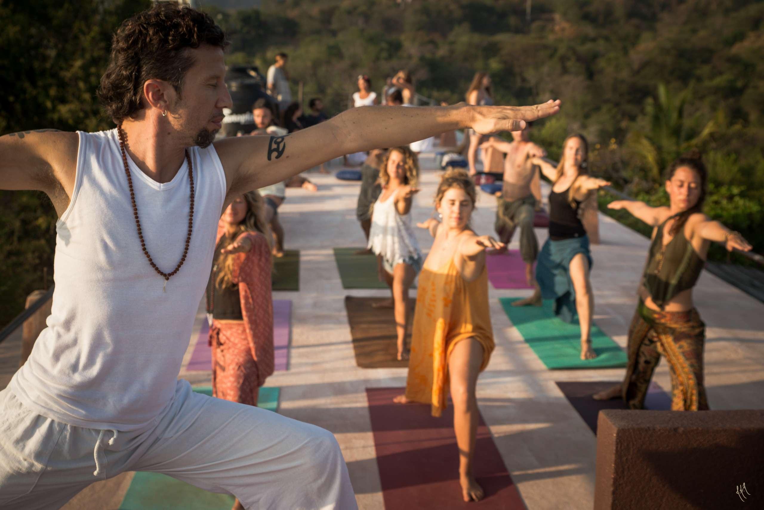male senior yoga teacher Marco leading an outdoor yoga class