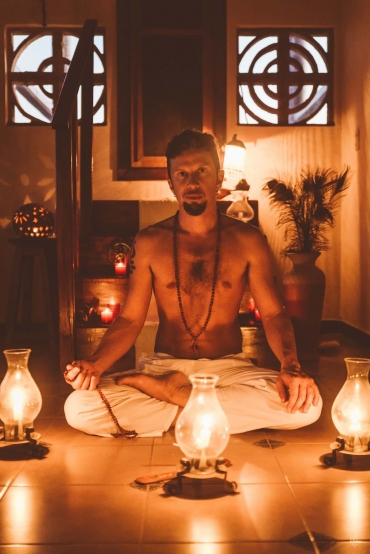 Tantric man sitting in meditative position surrounded by candles teaching tantric online courses