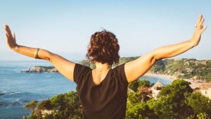 woman opening the arms looking at the sea and nature