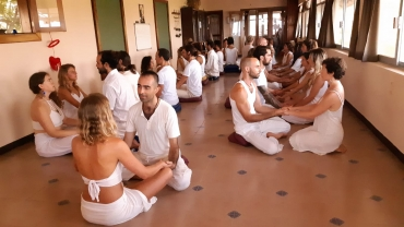 people sitting on the floor in front of each other holding hands at tantra workshops
